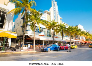 SOUTH BEACH MIAMI, FLORIDA - APRIL 25, 2016: View along the famous vacation and tourist location on Ocean Drive in the Art Deco district of South Beach, Miami on a sunny day with cars and palm trees.
