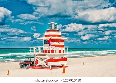 South Beach, Miami, Florida, lifeguard house in a colorful Art Deco style white and red on cloudy blue sky and Atlantic Ocean in background, world famous travel location