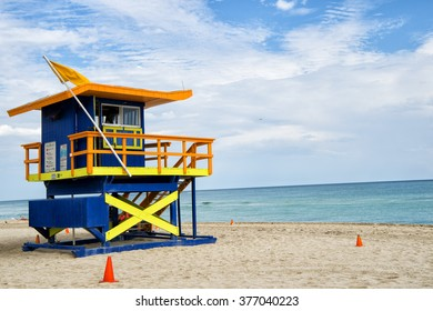 South Beach, Miami, Florida, lifeguard house in a typical colorful Art Deco style on cloudy day with blue sky and Atlantic Ocean in background, world famous travel location