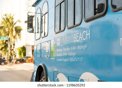 South Beach, USA - May, 2018: Blue Miami Beach Trolley, bus, vehicle offering free ride on road, street, intersection with driver windows, mirror in Florida