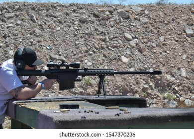 South Boulder City, Nevada / USA - April 30 2017: One adult man training with sniper barrett rifle at shooting range with instructor in desert