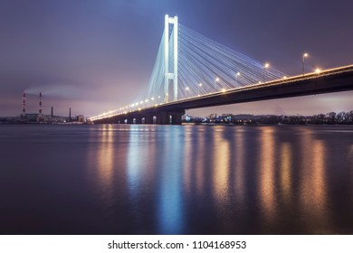 The South bridge at night, Kiev, Ukraine. Bridge at sunset across the Dnieper River. Kiev bridge against the backdrop of a beautiful sunset in Kiev. Bridge in evening sunshine.