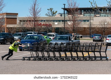 SOUTH BURLINGTON, VT, USA. May 14, 2020. South Burlington, VT A grocery store employee wearing a mask pushes carts back into the store.
