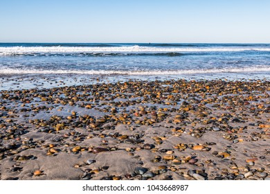 South Carlsbad State Beach in San Diego, California with colorful stones covering the beach.