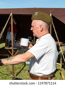 South Cerney Airfield, Gloucestshire Sept 2018. Vintage fair. Veteran holding a cup of tea with cap on in sunlight, portrait, isolated
