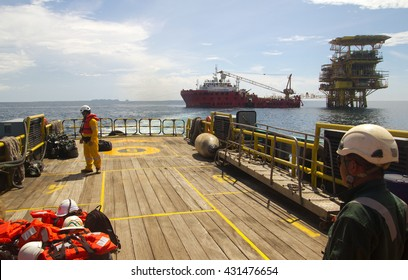 SOUTH CHINA SEA, BRUNEI - JUNE 11, 2013: Rig workers are transported by boat to offshore rigs in The South China Sea, Brunei on June 11, 2013. Swing ropes are used to enter the platform