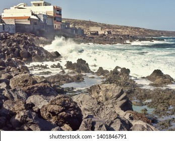 south coast of Tenerife with lava rock beach and lava rocks Two box-shaped houses typical of this Island  are located directly on the rocks on the coast, otherwise only Malpais, simple bushland.