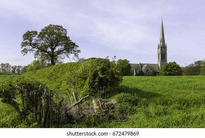 South Dalton, Yorkshire, UK. St Marys Church flanked by hedges, trees and a wheat field on a sunny morning in the village of South Dalton, near Beverley, Yorkshire, UK.