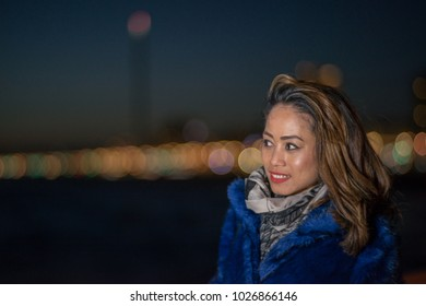 South east asian filipino female model keeps warm in the wintertime on a peer in the south of England