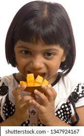 South East Asian six year old baby girl eating Mango