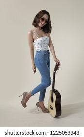 South East Asian woman full body posing with acoustic guitar, in flower print on white camisole top and high waist skinny distressed vintage blue washed denim on the beige background.