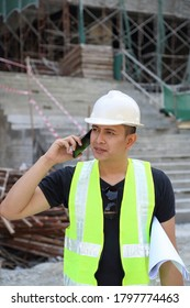 South East Asian young Malay man wearing white safety helmet yellow vest talking on phone