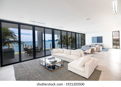 South Florida - April 2020: Expansive and spacious living area with wide views of the bay and city. Bright minimalist white interior with floor to ceiling glass windows.