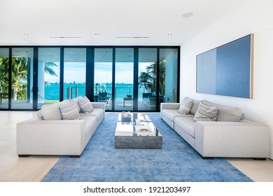 South Florida - April 2020: Modern living area with wide views of the bay and city. Bright minimalist white interior with designer sofas and floor to ceiling glass windows.