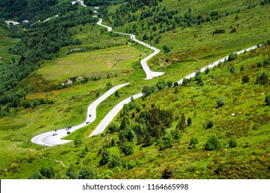 South of France: Panorama view of steep curvy serpentine road up to the border of Andorra with green fields and trees in the rocky mountains of the famous French Pyrenees - concept transport travel
