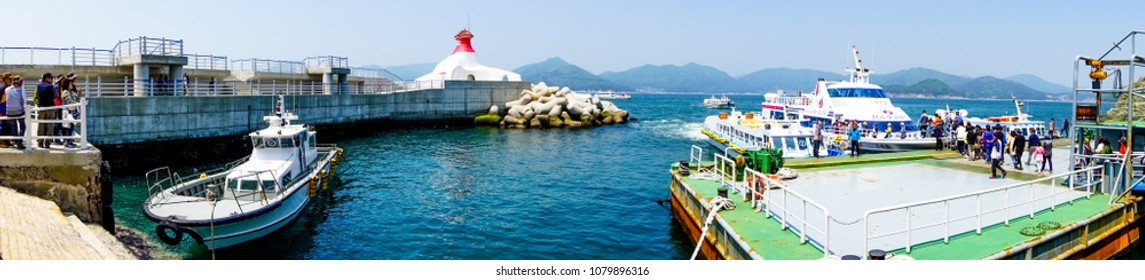 SOUTH GYEONGSANG, SOUTH KOREA - April 28, 2018 : Ferry wharf and lighthouse of Oedo Botania island in the southern region of Geoje islands with many tourist transfer on the floating pontoon.