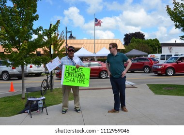 SOUTH HAVEN, MI / USA - AUGUST 12, 2017: An activist encourages visitors to the National Blueberry Festival in downtown South Haven to sign a petition to legalize marijuana in Michigan.