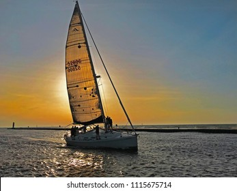 South Haven, Michigan, USA – June 8, 2018:  A sailboat at sunset traveling up the black river from Lake Michigan towards the harbor in South Haven, Michigan, USA with blue sky copy space.