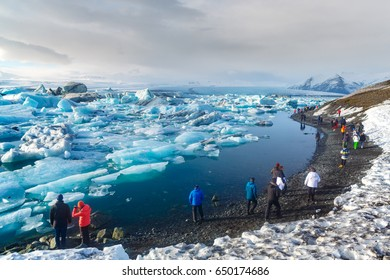 South Iceland - March 12, 2017. Tourist walking along glacier lagoon, Jokulsarlon, Iceland