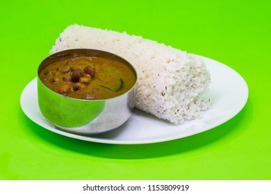 South Indian breakfast puttu made of steamed rice flour and coconut with delicious kadala curry or chana masala isolated in a green background, Kerala, India.