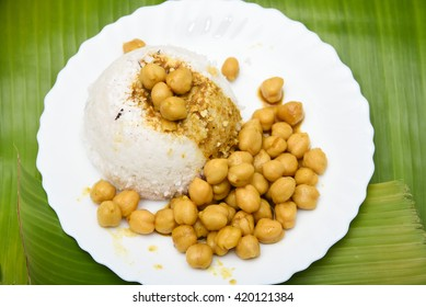 South Indian breakfast puttu / pittu made of rice flour and coconut, Kerala, India. White puttu with chickpea / lentil curry.