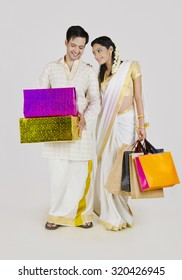 South Indian couple with shopping bags and gifts