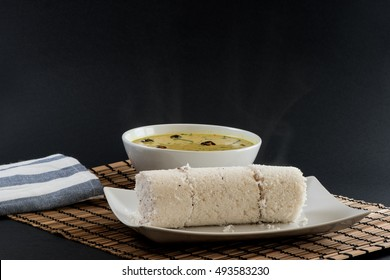 South Indian dish puttu with curry on black background
