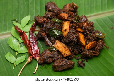 South Indian dish spicy beef fry Kerala, India. side dish ghee rice, appam, parotta, puttu, bread and chappathi, Kerala cuisine ,Buffalo roast / Meat pepper fry with coconut. India spices cooking,
