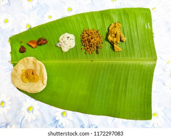 South Indian lunch on plantain leaf, top down composition. Curries are served in one half, rice in the other. Overhead view of Kerala sadya on plantain leaf.