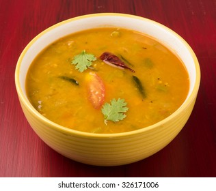 south indian vegetable sambar, in ceramic bowl on red wooden background
