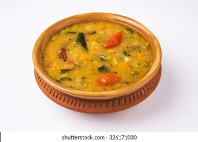 south indian vegetable sambar, in a terracotta bowl on white background