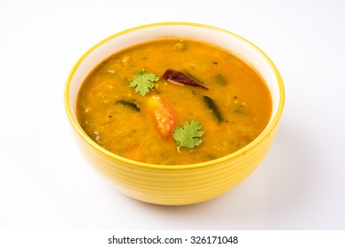 south indian vegetable sambar, in yellow ceramic bowl on white background