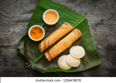 South Indian Vegetarian meal paper Masala Dosa chutney and sambar on Banana leaf overhead view / Veg Thali