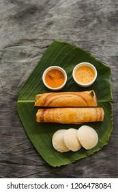 South Indian Vegetarian meal paper Masala Dosa chutney and sambar on Banana leaf overhead view / Veg Thali