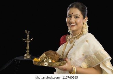 A South Indian woman holding a plate of religious offerings