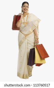 South Indian woman holding shopping bags and smiling