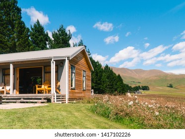 South Island, New Zealand - Jan 2019: Wooden cabin lodge & deck terrace. Countryside background. Beautiful wood interior design. Holiday vacation cottage. Architecture, eco, travel, retreat concepts