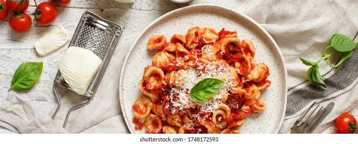 South italian  pasta orecchiette with tomato sauce and cacioricotta cheese top view on a white table