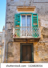 South Italy, Venosa Basilicata, Old building with ruined facade with colorful green broken wooden window shutter and vintage iron balcony.