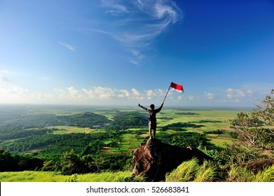 South Kalimantan, Indonesia: 17 May 2015 - A man stand with Indonesia flag stands on top of Lebak Naga Hill, Tanah Laut.