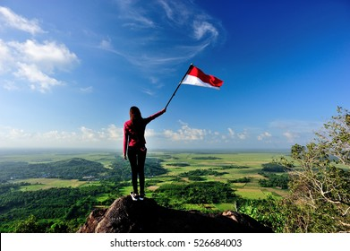 South Kalimantan, Indonesia: 17 May 2015 - A girl stand with Indonesia flag stands on top of Lebak Naga Hill, Tanah Laut.