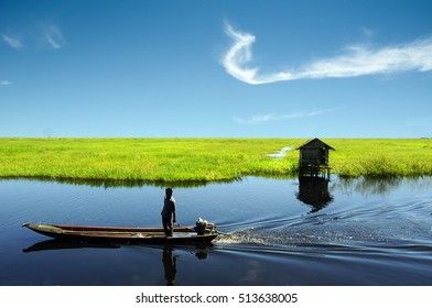 South Kalimantan, Indonesia - February 10, 2008: A man stands on his traditional boat near an abandoned house at Nagara City.