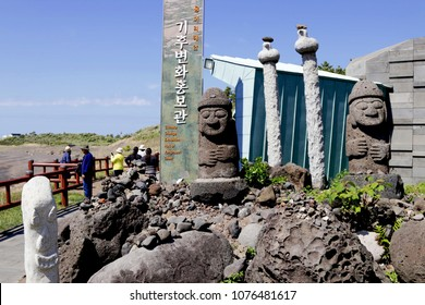 """South Korea - April 2018 :  Dol hareubangs stone ,symbol of Jeju do,at Yongmeori beach with tourists on background. The large rock statues ,meaning """"Old Grandfather"""",found on Jeju Island,South Korea ."""