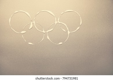 South Korea -February 9, 2018: Winter Olympic Games symbol rings on the metalic golden background