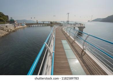 South Korea, November 10, 2017: People are seen walking on Busan's Songdo Skywalk, the longest skywalk on the water in South Korea. Visitors can see the ocean under their feet through glass floors.