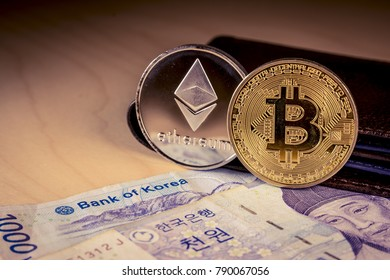 South Korean won currency with the words bank of korea focused and physical bitcoin and ethereum coins. Business concept.