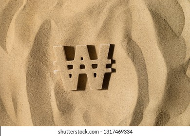 South Korean Won Symbol or Sign Covered with Sand in the Sun after Crisis