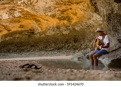 SOUTH KUTA, INDONESIA - OCT 17, 2013: Local singer songwriter plays guitar and harmonica on the beach.
