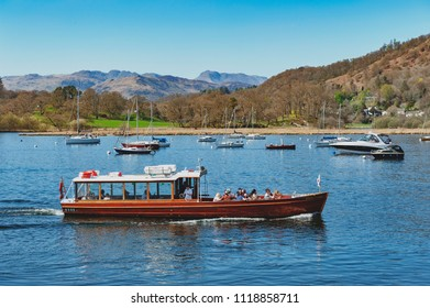 South Lakeland, UK - April 2018: Tourist boat cruise at Waterhead Pier in Ambleside, a lakeside town situated at the head of Windermere Lake within the Lake District National Park in England