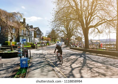 South Lakeland, UK - April 2018: Cyclist on the lakeside street at Ambleside, a small lakeside town situated at the head of Windermere Lake within the Lake District National Park in England